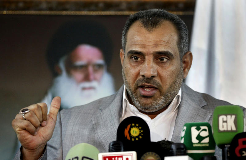 Adnan Faihan, the head of the political bureau of the Asaib Ahl al-Haq group, speaks during a press conference in Baghdad, Iraq, Wednesday, May 29, 2013. The senior member of an Iraqi Shiite militia that once fought the U.S. military warned on Wednesday that Iraq is heading toward widespread sectarian bloodletting similar to the kind that once pushed the country to the brink of civil war. Poster in the back shows late Ayatollah Mohammed Sadiq al-Sadr, father of the radical anti-US cleric Muqtada al-Sadr. (AP Photo/ Hadi Mizban)
