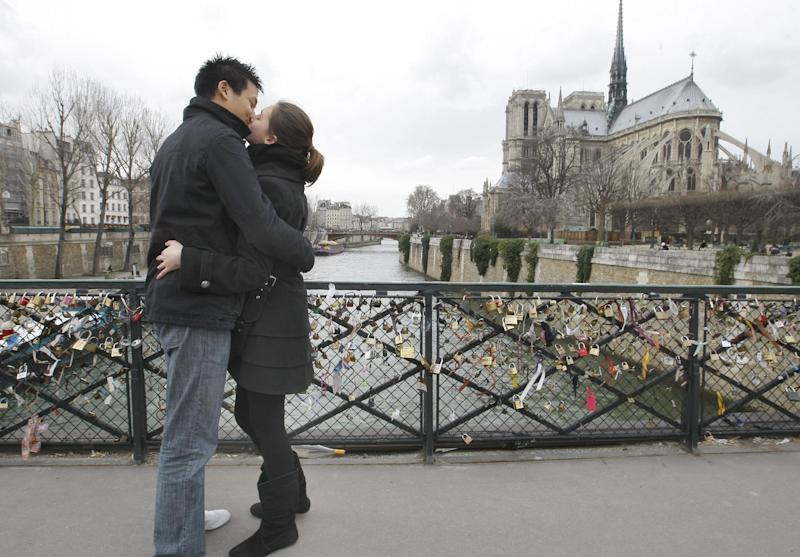 "FILE - This Feb. 14, 2011 file photo shows French lovers, David, 22 and Charlene, 23, exchanging a kiss on Valentine's day in front of Notre-Dame cathedral in Paris, France. After centuries of lacking a French word for the sloppy Gallic export ""to French kiss,"" a verb has finally been given its rightful place in the French dictionary. ""Galocher"", to kiss with tongues, is among new entries added to the ""Petit Robert"" 2014 edition, which hits the shops Thursday. (AP Photo/Jacques Brinon, File)"