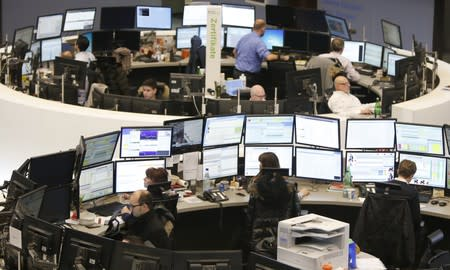 FILE PHOTO: Traders work at their screens at the stock exchange in Frankfurt