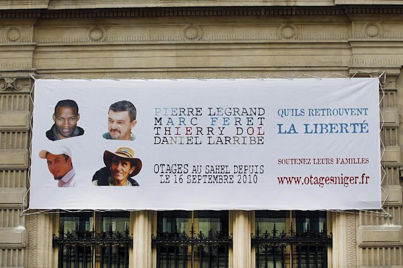 FILE - This Monday Sept. 16, 2013, file photo shows a banner with the portraits of the French hostages that were kidnapped in Niger three years ago, set up on the fourth district city hall in Paris, France. President Francois Hollande says four Frenchmen taken hostage by Islamic extremists in Niger have been released. The four were taken in September 2010 from their dormitories in the town of Arlit, where they worked for the French nuclear company Areva. The portraits show from top left, clockwise: Thierry Dol, Marc Feret, Daniel Larribe, Pierre Legrand, and reads: May They Recover Freedom. (AP Photo/Remy de la Mauviniere, File)