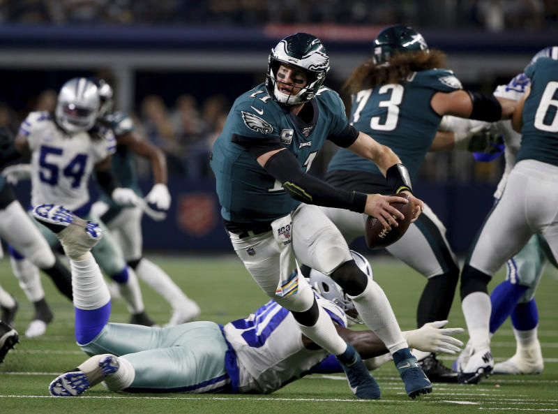 Philadelphia Eagles quarterback Carson Wentz (11) escapes pressure from Dallas Cowboys defensive end Demarcus Lawrence, bottom rear, in the second half of an NFL football game in Arlington, Texas, Sunday, Oct. 20, 2019. (AP Photo/Ron Jenkins)