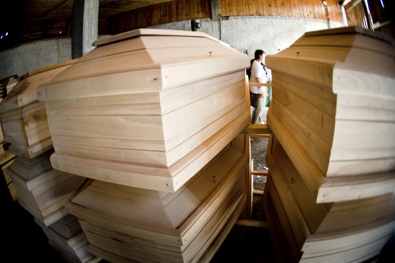 Coffins are stored in a warehouse in Talmaciu, central Romania, on Sept. 16, 2011. Times are so hard in Romania that people joke they cannot afford to die, but in a dark workshop in the mountains of Transylvania, carpenters are churning out cut-price coffins, in a bid to beat the rising costs of death.(AP Photo/Vadim Ghirda)