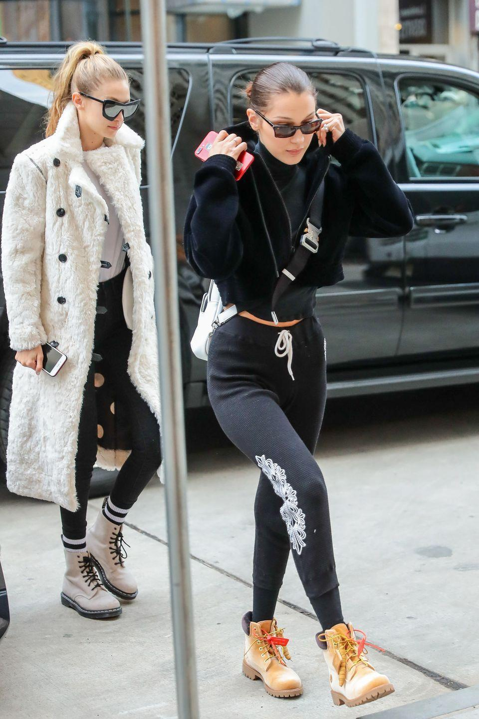 <p>Bella wears a cropped bomber jacket and black turtleneck, black waffle sweatpants, sunglasses, crossbody bag, and Timberland boots while out in NYC. Gigi follows close behind with a furry white coat, white tee, leggings, tube socks, Dr. Martens boots, and oversized sunglasses.</p>