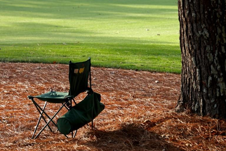 An empty Masters chair from last year summed up the lack of spectators at the event due to Covid-19 precautions, with course marshals among the few to sit and watch players compete for a green jacket