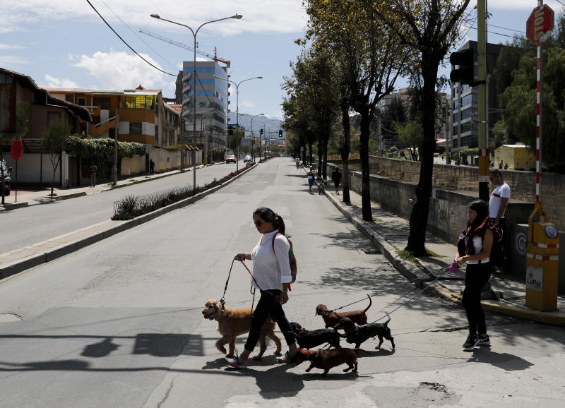 Women walk their dogs during general elections in La Paz, Bolivia, Sunday, Oct. 20, 2019. Bolivians are voting in general elections Sunday where President Evo Morales is candidate for a fourth term. (AP Photo/Jorge Saenz)