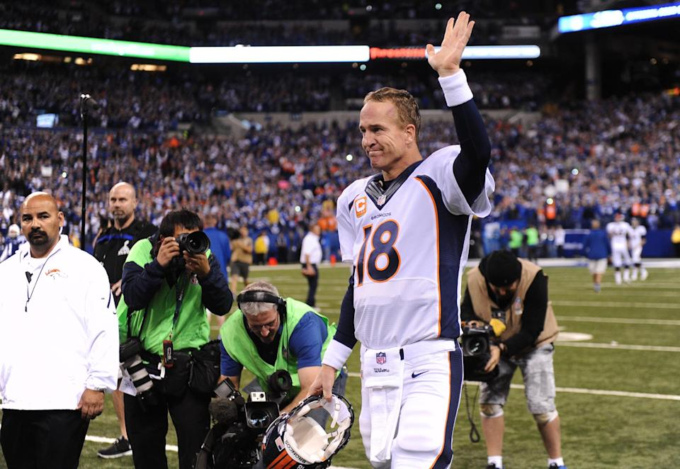 Broncos quarterback Peyton Manning waves to the crowd as he is honored on the field before the game in his return to Indianapolis on Oct. 20, 2013.