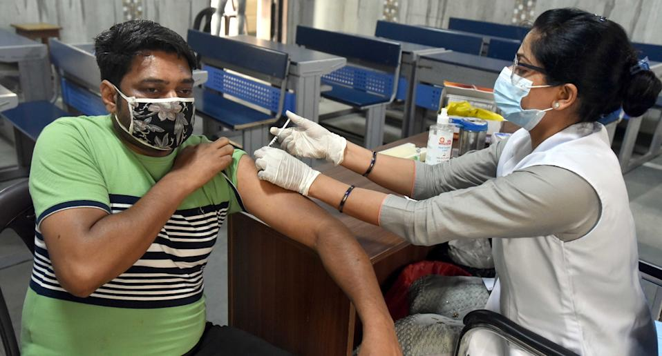 A health worker administers a dose of Covid vaccine to a beneficiary, during a vaccination drive for the age group of 18 to 44, at a government school, on May 17, 2021 in New Delhi. Photo: Sonu Mehta/Hindustan Times via Getty Images