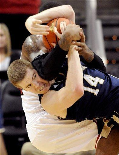 Notre Dame's Scott Martin, front, battles Louisville's Shane Behanan for a loose ball during the second half of their NCAA college basketball game, Saturday, Jan. 7, 2012, in Louisville, Ky. Notre Dame won 67-65 in double overtime. (AP Photo/Timothy D. Easley)