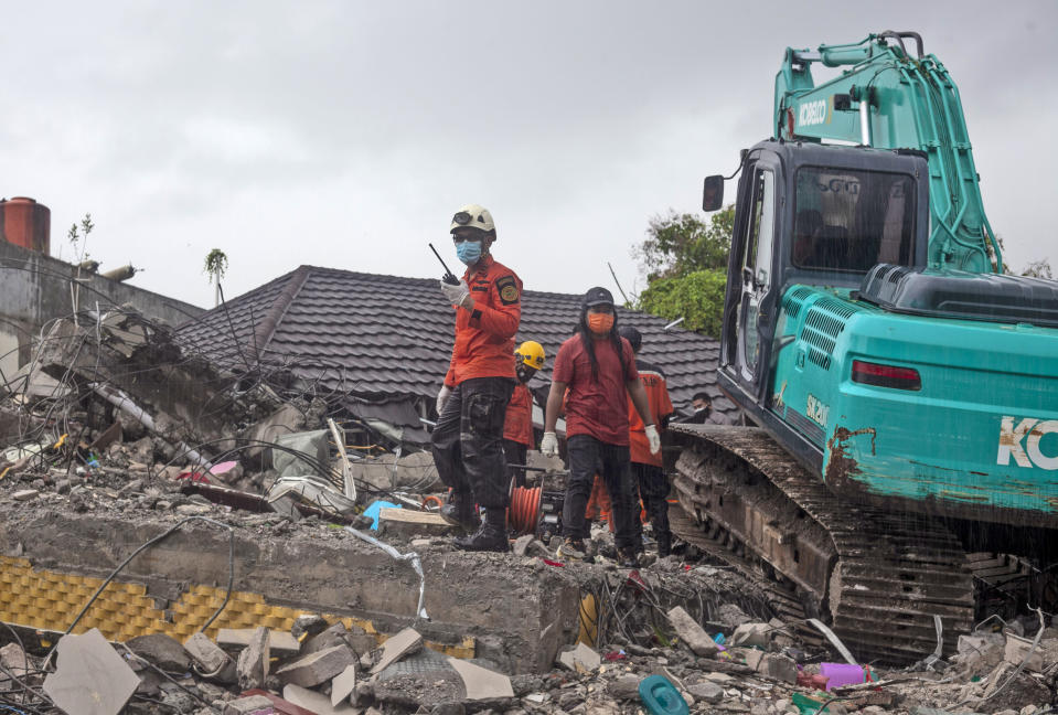 Rescuers search for survivors among the ruin of a building damaged by an earthquake in Mamuju, West Sulawesi, Indonesia, Friday, Jan. 15, 2021. A strong, shallow earthquake shook Indonesia's Sulawesi island just after midnight Friday, toppling homes and buildings, triggering landslides and killing a number of people. (AP Photo/Yusuf Wahil)