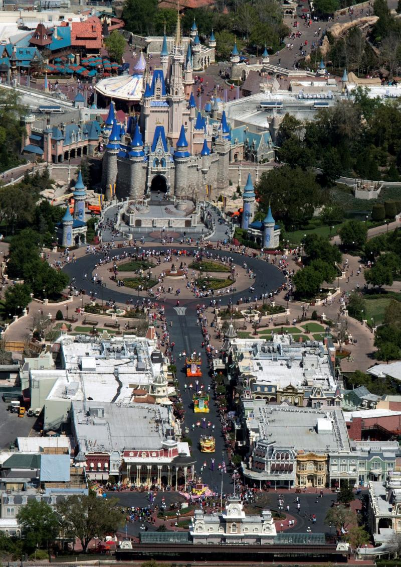 Guests line up to watch a parade along Main Street at Disney's Magic Kingdom on the final day before closing in an effort to combat the spread of coronavirus disease (COVID-19), in an aerial view in Orlando, Florida, U.S. March 15, 2020. Picture taken March 15, 2020. REUTERS/Gregg Newton