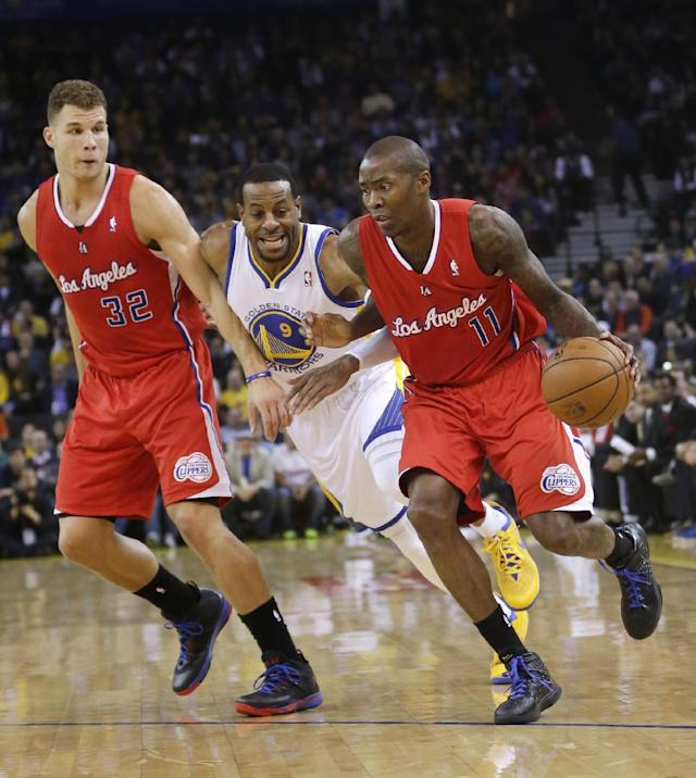 Los Angeles Clippers' Jamal Crawford (11) dribbles around a screen on Golden State Warriors' Andre Iguodala (9) set by Blake Griffin (32) during the first half of an NBA basketball game Thursday, Jan. 30, 2014, in Oakland, Calif. (AP Photo)
