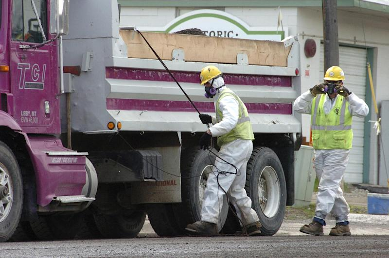 FILE - In this April 28, 2011 file photo, unidentified road workers wear protective gear against possible asbestos contamination as they load material from a road resurfacing project in downtown Libby, Mont. W.R. Grace, Inc., the chemical company blamed for polluting Libby, Mont. with asbestos dust that has killed hundreds of people, is pushing back against the Environmental Agency proposal and seeking to have it revised. Attorneys and scientists for W.R. Grace Inc., which operated an asbestos mine in Libby for three decades, say the EPA proposal would frustrate cleanup efforts by setting an unattainable standard for exposures. (AP Photo/Matthew Brown)