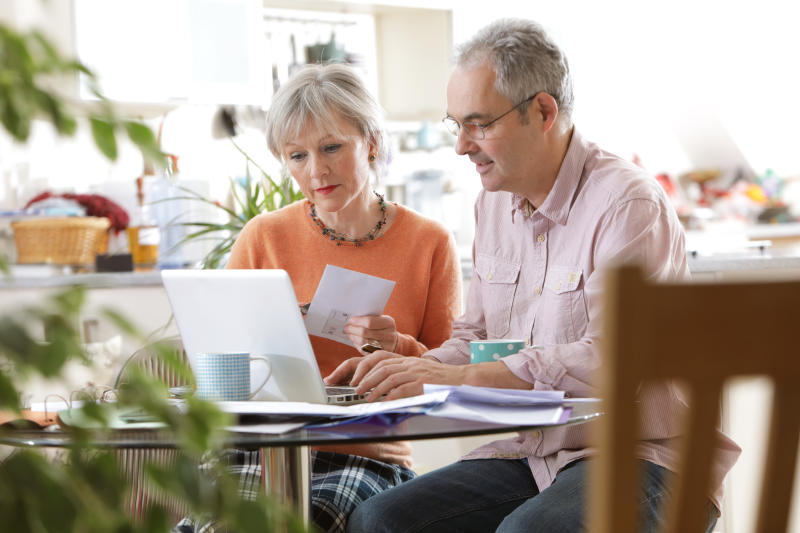 Older couple sat at home looking at laptop