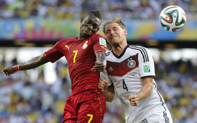 Ghana's Christian Atsu, left, battles for the ball with Germany's Benedikt Hoewedes during the group G World Cup soccer match at the Arena Castelao in Fortaleza, Brazil, Saturday, June 21, 2014. (AP Photo/Frank Augstein)
