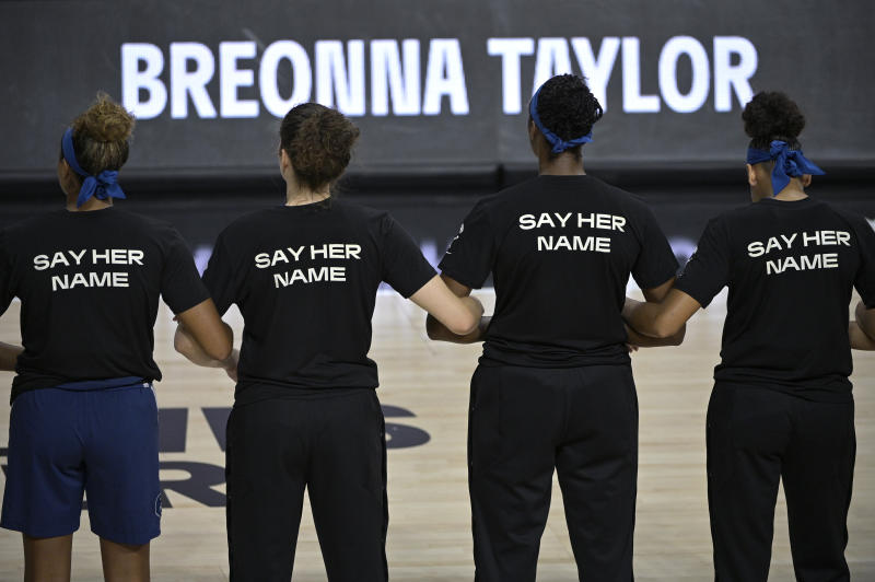 "Minnesota Lynx players lock arms with black T-shirts on that say ""Say Her Name."""
