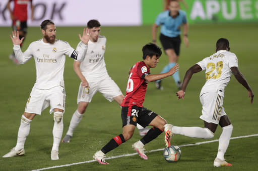 Mallorca's Takefusa Kubo, center, vies for the ball with Real Madrid's Ferland Mendy, right, during the Spanish La Liga soccer match between Real Madrid and Mallorca at Alfredo di Stefano stadium in Madrid, Spain, Wednesday, June 24, 2020. (AP Photo/Bernat Armangue)
