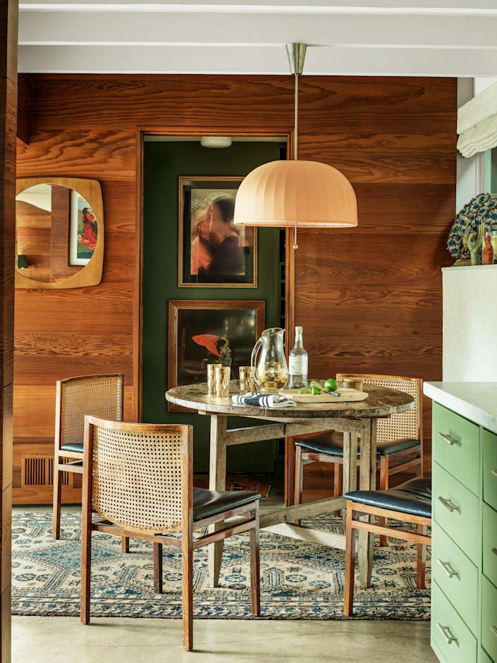 In the kitchen, a vintage Hans-Agne Jakobsson ceiling fixture hangs over an antique table and Tito Agnoli chairs.