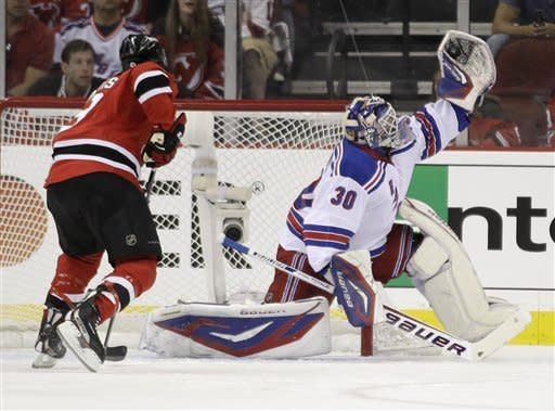New York Rangers goalie Henrik Lundqvist, right, of Sweden, stops a shot as New Jersey Devils right wing Dainius Zubrus, of Lithuania, looks for a rebound during the first period of Game 3 of the NHL hockey Stanley Cup Eastern Conference final playoff series, Saturday, May 19, 2012, in Newark, N.J.  (AP Photo/Julio Cortez)