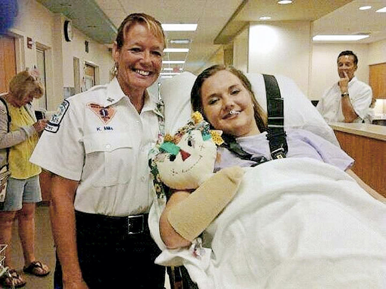 In this image released Monday, July 2, 2012, by Tom Adkins, shows Aimee Copeland, right, with medic Kori Mills as Copeland leaves a hospital in Augusta Ga., headed for an inpatient rehabilitation clinic. Copeland left a Georgia hospital just weeks after a flesh-eating disease took her limbs but not her life. After nearly two months of battling the rare infection, called necrotizing fasciitis, Copeland headed to an inpatient rehabilitation clinic, where she'll learn to use a wheelchair after having her left leg, right foot and both hands amputated. (AP Photo/Tom Adkins)