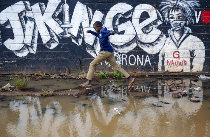A boy steps across a flooded area next to an informational mural with words in Swahili advising people to protect themselves from the coronavirus and get vaccinated, in the low-income Kibera neighborhood of Nairobi, Kenya, Saturday, June 12, 2021. Africa's 1.3 billion people account for 18% of the world's population. But the continent has received only 2% of all vaccine doses administered globally. (AP Photo/Brian Inganga)