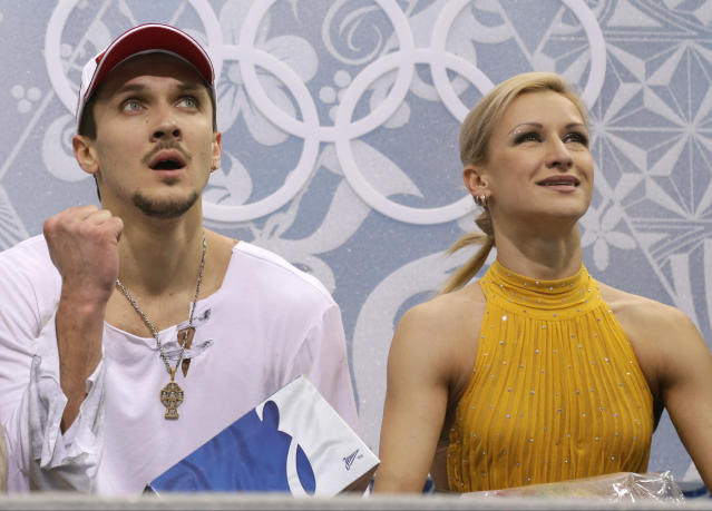 Tatiana Volosozhar and Maxim Trankov of Russia wait in the results area after competing in the pairs free skate figure skating competition at the Iceberg Skating Palace during the 2014 Winter Olympics, Wednesday, Feb. 12, 2014, in Sochi, Russia. (AP Photo/Darron Cummings)