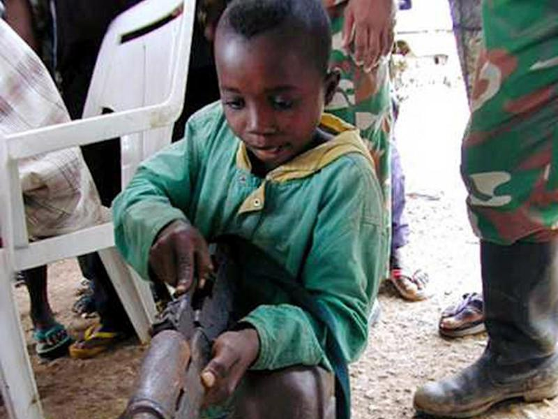 A child soldier plays with a weapon returned by a combatant in Freetown, Sierra Leone in 2001 (AFP/Getty Images)