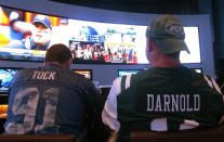 FILE: This Sept. 9, 2018 file photo shows fans of the New York Giants and Jets watching a football game after placing bets in the sports betting lounge at the Ocean Casino Resort in Atlantic City, N.J. The American Gaming Association projects that 45.2 million Americans will bet on the NFL this season. (AP Photo/Wayne Parry, FILE)