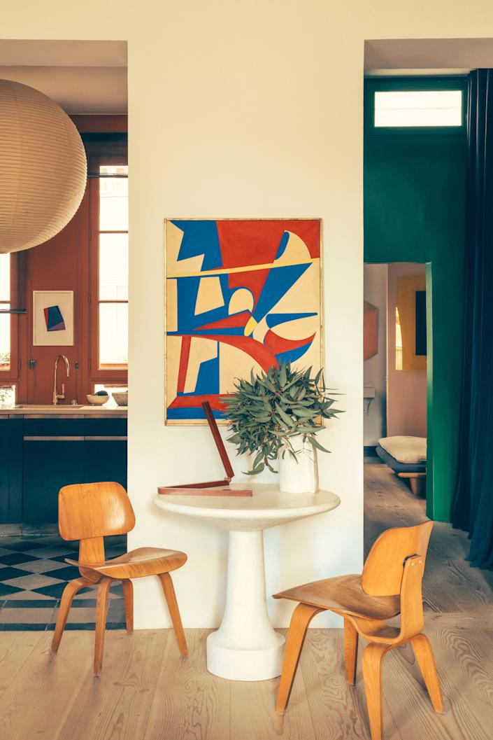 """<div class=""""caption""""> In the salon, a Noguchi lantern hangs to the left and a circa 1960 Italian painting is on the wall. The chairs are LCW by Charles and Ray Eames. </div>"""