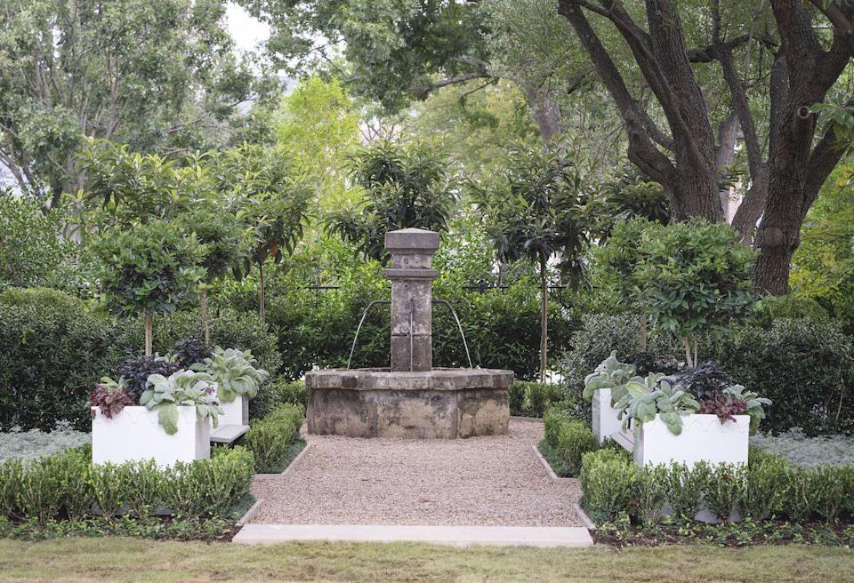 """<p>Houchard really had his work cut out for him with a landscaping project that needed to take place during the dog days of a Dallas summer. However, Daniel Houchard of <a href=""""https://www.fromthegrounduplandscape.com/"""" rel=""""nofollow noopener"""" target=""""_blank"""" data-ylk=""""slk:From the Ground Up Landscape"""" class=""""link rapid-noclick-resp"""">From the Ground Up Landscape</a> was clearly up for the challenge as his elegant designs feel elegant and appropriate for any and all seasons in the state of Texas. He says the property is filled with beautiful, mature oak and magnolia trees which was a perfect starting off point for his team to create a soothing, welcoming space that may cause guests to linger for a few moments before arriving at the front door.</p><p>""""There's a sense of majestic-ness to the landscape that matched the scale of the house, and we couldn't have created it even if we were able to crane in trees,"""" says Houchard. """"The challenge is that the front yard can easily be a throwaway space because of the driveway and the foundation planning, but we really wanted to create an exterior foyer to the home that initiated a pause as one enters and exits. It isn't a pass-through but its own destination.""""</p><p>Houchard and his team wanted to create a classic Southern garden to complement the architecture of the home and utilized plantings typically found in these spaces like clipped boxwood hedges, azaleas, and holly that are durable and hardy but bring in a variety of colors and textures. He also discovered a stunning 19th century water feature that draws you into his exterior foyer long before you actually see it. The path to the fountain is lined with zinc finish and stone resin planters from <a href=""""https://www.pennoyernewman.com/"""" rel=""""nofollow noopener"""" target=""""_blank"""" data-ylk=""""slk:Pennoyer Newman"""" class=""""link rapid-noclick-resp"""">Pennoyer Newman</a> and benches from Currey and Company along the gravel pathway.</p><p>Once the exterior brick was painted white, Houch"""