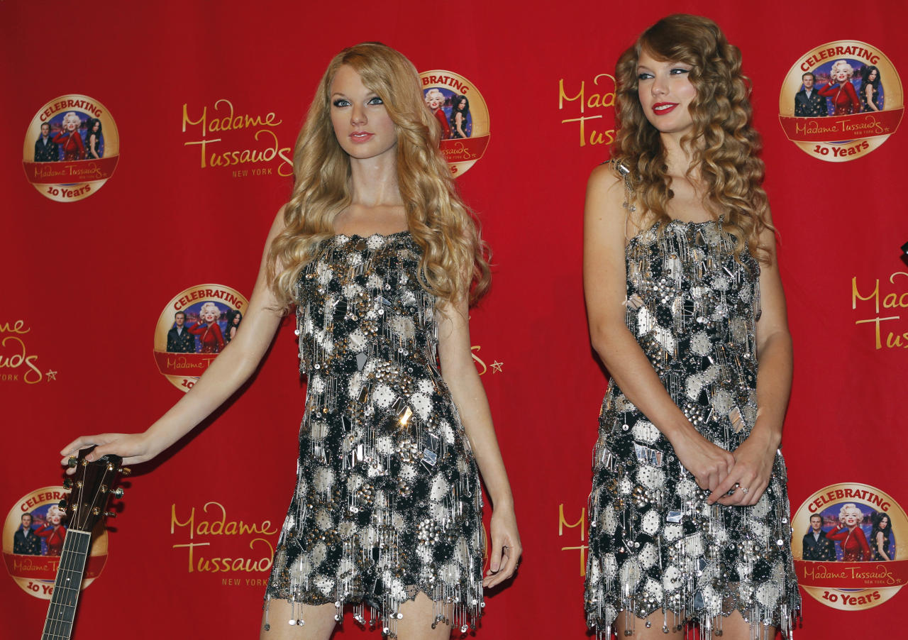Singer and songwriter Taylor Swift (R) smiles as she poses with her wax likeness during an unveiling of the statue at Madame Tussauds in New York, October 27, 2010. REUTERS/Mike Segar