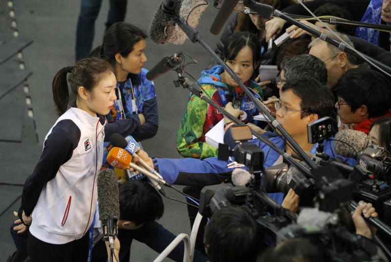 Yuna Kim of South Korea, left, speaks with the media after a training session at the figure skating practice rink at the 2014 Winter Olympics, Thursday, Feb. 13, 2014, in Sochi, Russia. (AP Photo/Vadim Ghirda)