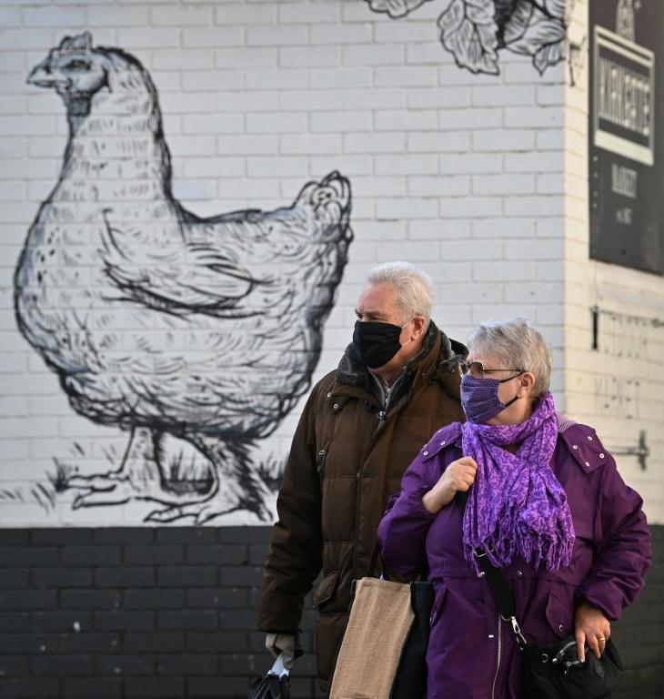 Shoppers walk past a mural at Kirkgate Market in Leeds on October 31, 2020, as the number of cases of the novel coronavirus COVID-19 rises.