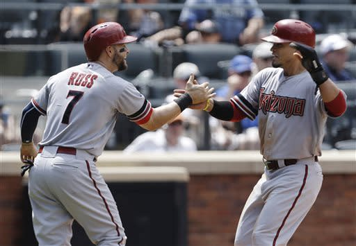 Arizona Diamondbacks' Cody Ross, left, and Gerardo Parra, right, celebrate after scoring on a single by Wil Nieves during the fifth inning of a baseball game against the New York Mets on Thursday, July 4, 2013, in New York. (AP Photo/Frank Franklin II)