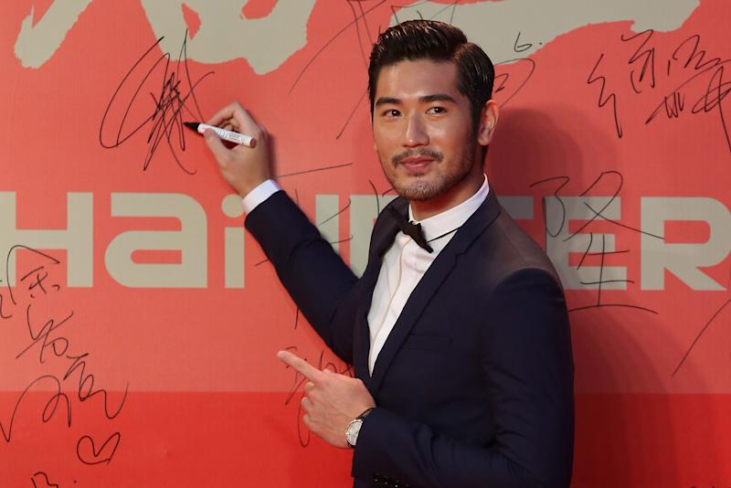 Godfrey Gao signs a poster