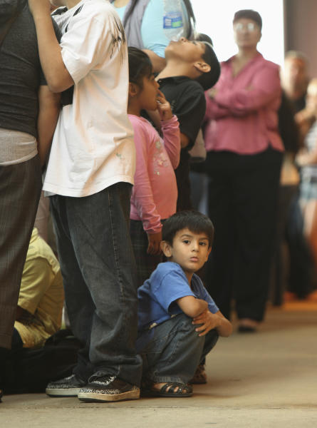 Children stand in line with some of the thousands of young immigrants at Chicago's Navy Pier on Wednesday, Aug. 15, 2012, waiting for guidance with a new federal program that would help them work legally in the United States and avoid deportation. At least 11,000 people showed up for the workshop led by immigrant rights advocates for help in putting together identity documents and filling out the detailed forms on the first day that the federal government began accepting applications. (AP Photo/Sitthixay Ditthavong)