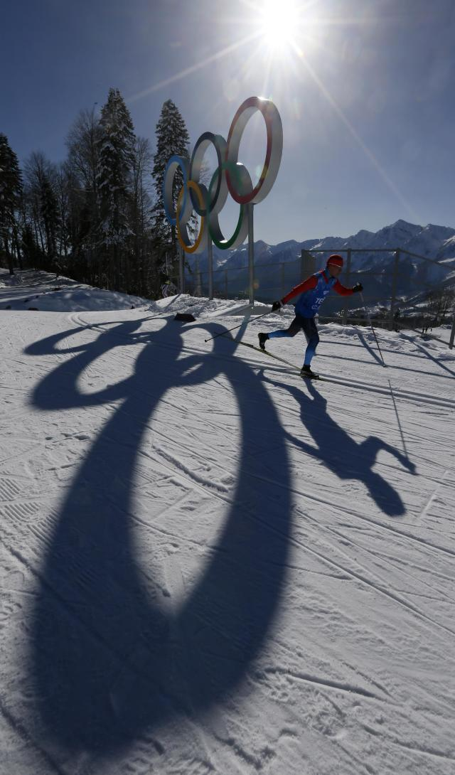 An unidentified Cross Country skier passes by the Olympic rings in the Cross Country stadium of the 2014 Winter Olympics, Tuesday, Feb. 4, 2014, in Krasnaya Polyana, Russia. (AP Photo/Dmitry Lovetsky)