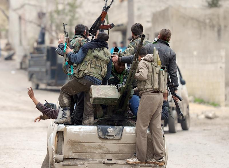 Syrian rebel fighters celebrate after taking over the village of Aljanodiya, northwestern Idlib province, following fighting against pro-Syrian regime forces, on January 30, 2013