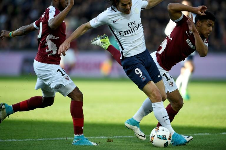 Metz' defender Matthieu Udol (R) vies for the ball with Paris Saint-Germain's forward Edinson Cavani (C) during the French L1 football match between Metz and PSG on April 18, 2017