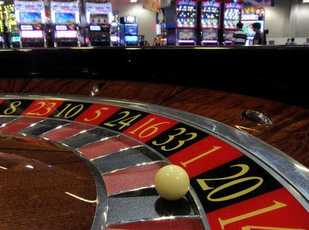 FILE PHOTO: Ball is seen on a roulette wheel in front of slot machines at Gaming Expo Asia in Macau