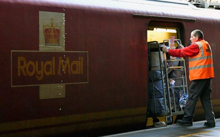 Royal Mail employee loads packages onto train