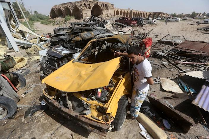 An Iraqi man stands next to the wreckage of cars in the aftermath of a massive suicide bomb attack carried out by the Islamic State group in the predominantly Shiite town of Khan Bani Saad, on July 18, 2015 (AFP Photo/Ahmad al-Rubaye)