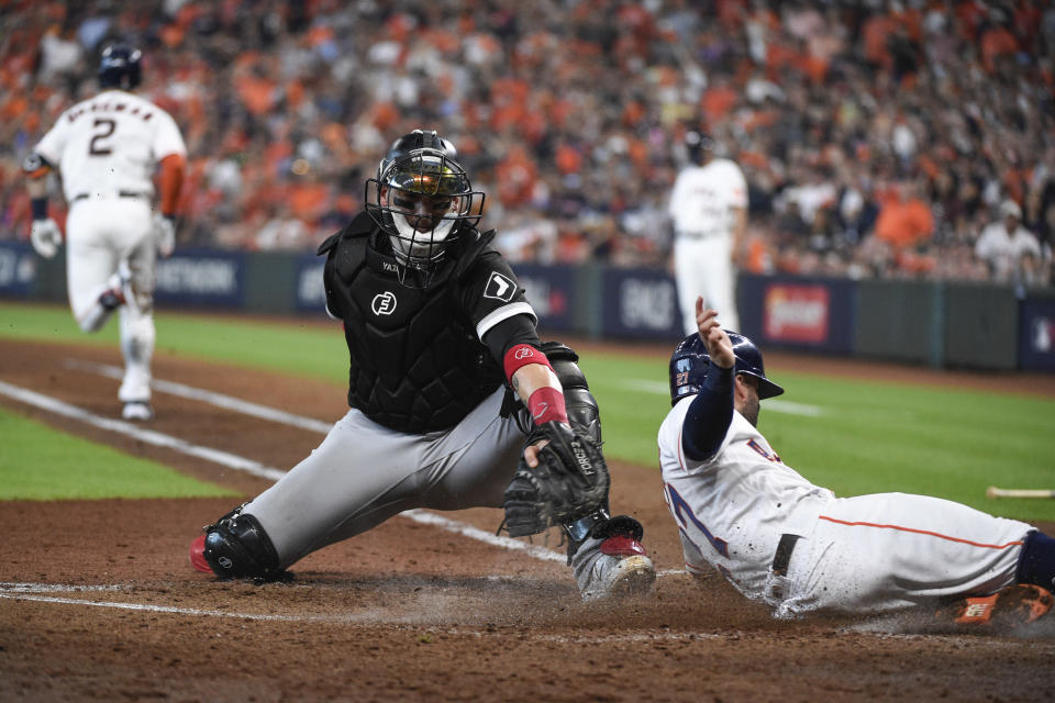 Houston Astros' Jose Altuve, right, slides at home plate while scoring ahead of the tag by Chicago White Sox catcher Yasmani Grandal, center, on a fielder's choice ground ball by Alex Bregman (2) during the third inning in Game 1 of a baseball American League Division Series Thursday, Oct. 7, 2021, in Houston. (AP Photo/Eric Christian Smith)