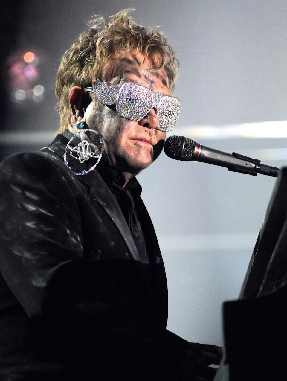 <p>Elton John performs at the 2010 Grammy Awards in a bedazzeled earring and glasses. (Photo: Getty Images) </p>