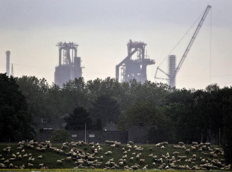 Sheep rest in front of furnaces in Duisburg, Germany, Tuesday, May 15, 2012. Germany's economy grew 0.5 percent in the first quarter of 2012. Europe dodged one bullet Tuesday after figures showed the economy of the 17 countries that use the euro narrowly avoiding recession in the first quarter of the year despite a raging debt crisis that's raising the specter of the breakup of the currency union. However, huge economic disparities exist across the single currency bloc, with many of those pursuing aggressive austerity programs mired in recession, while the powerhouse economy of Germany prospers on the back of its industrial might. (AP Photo/Frank Augstein)