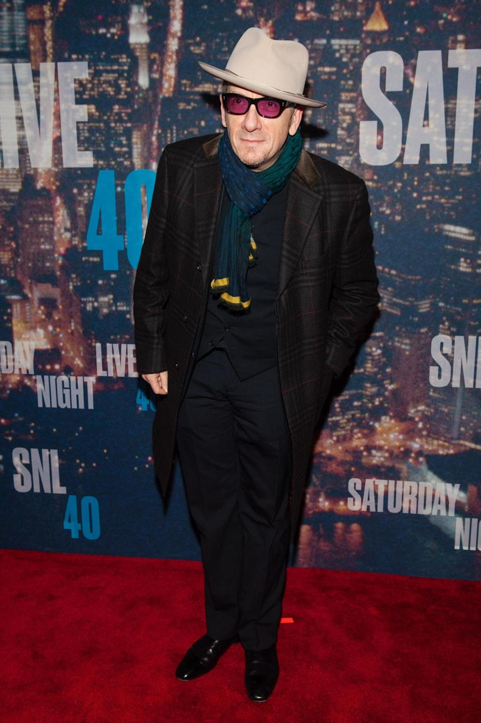 Elvis Costello must secretly be attending New York Fashion Week — or following along at home — because his outfit, from the wide-brimmed hat, to plaid coat, and tinted glasses, are just so trendy.