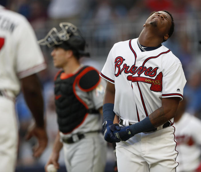 Atlanta Braves' Ronald Acuna Jr., right, reacts after being hit by a pitch from Miami Marlins'Jose Urena during the first inning of a baseball game Wednesday , Aug. 15, 2018 in Atlanta. Both dugouts emptied and Urena was ejected. Marlins catcher J.T. Realmuto is at rear. (AP Photo/John Bazemore)