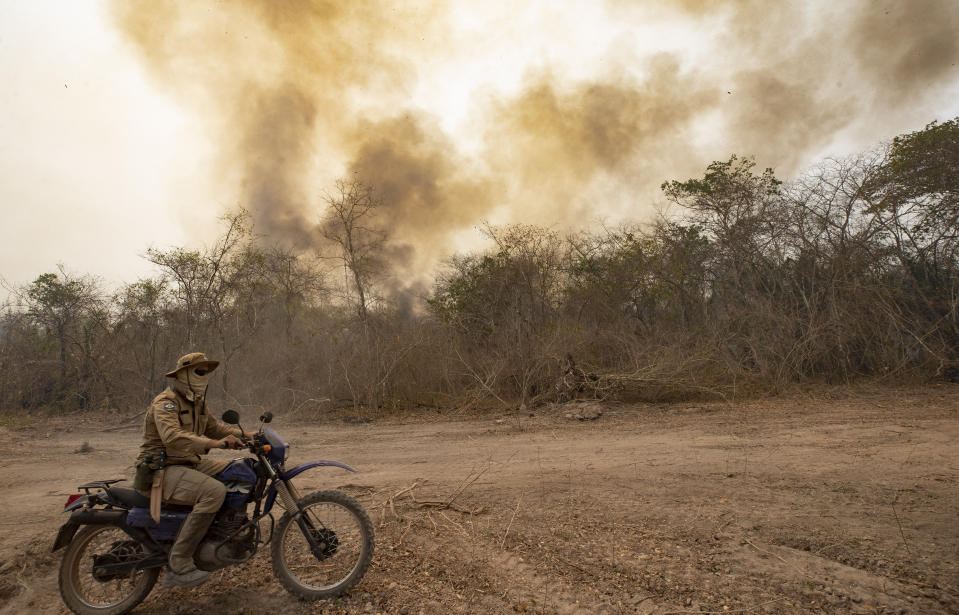 A firefighter rides a motorcycle past a burning area next to the Transpantaneira road at the Pantanal wetlands near Pocone, Mato Grosso state, Brazil, Monday, Sept. 14, 2020. A vast swath of the vital wetlands is burning in Brazil, sweeping across several national parks and obscuring the sun behind dense smoke. (AP Photo/Andre Penner)