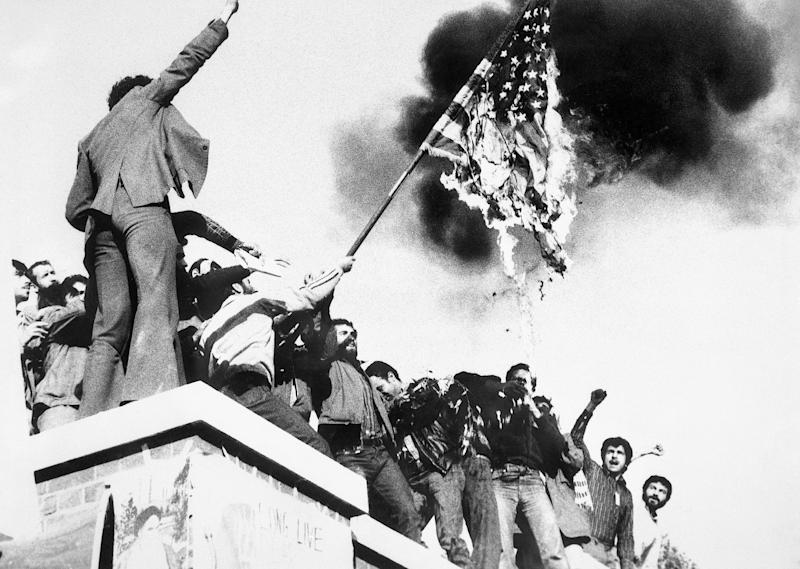 Image: Demonstrators perched atop of the United States Embassy wall burn an American flag, the fourth American flag to be burned since the students seized the embassy and more than 60 hostages (Bettmann Archive / Getty file)