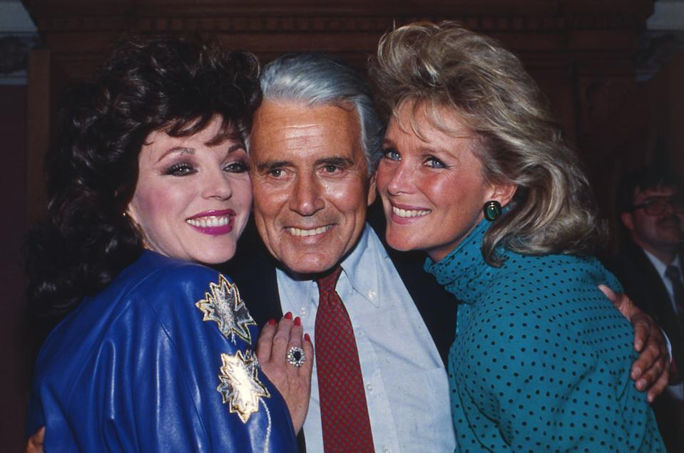 """Actor John Forsythe is joined by """"Dynasty"""" actresses Joan Collins, left and Linda Evans at a party celebrating the production of 150 episodes of the popular series in Los Angeles, USA, September 1986. (AP Photo/Reed Saxon)"""