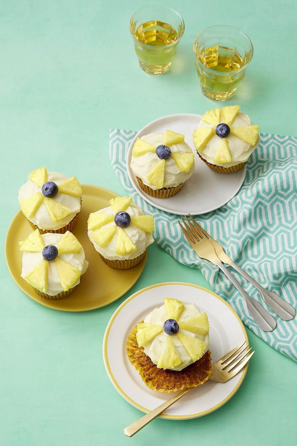 """<p>For a tropical dessert, try this cupcake recipe, which combines the flavors of pineapples and bananas and is decorated with pineapple and blueberry """"flowers.""""</p><p><strong><a href=""""https://www.womansday.com/food-recipes/food-drinks/a19123934/hummingbird-cupcake-recipe/"""" rel=""""nofollow noopener"""" target=""""_blank"""" data-ylk=""""slk:Get the Hummingbird Cupcakes recipe."""" class=""""link rapid-noclick-resp""""><em>Get the Hummingbird Cupcakes recipe.</em></a> </strong></p>"""